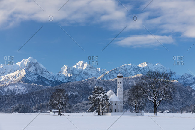 Pilgrimage church St. Coloman in winter against mountains, near Schwangau, Fuessen, Swabia, Ostallgaeu, Bavaria, Germany