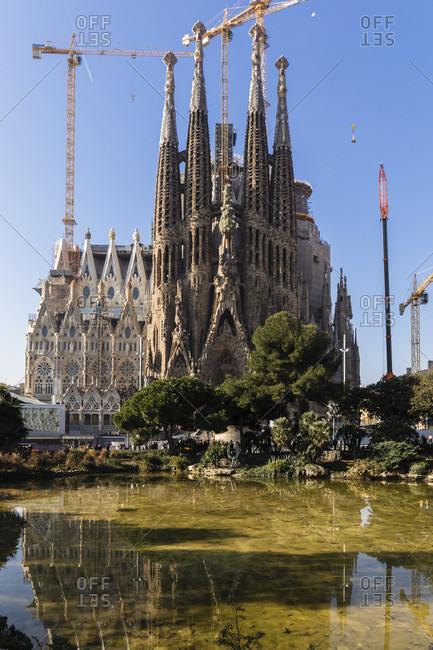 February 21, 2017: Cathedral La Sagrada Familia from Architect Antonio Gaudi reflecting in a pond, Nativity Facade, still under construction, UNESCO World Heritage Site, Barcelona, Catalonia, Spain