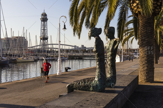 February 25, 2017: Sculptures in front of a jogger on the promenade, Barcelona, Catalonia, Spain