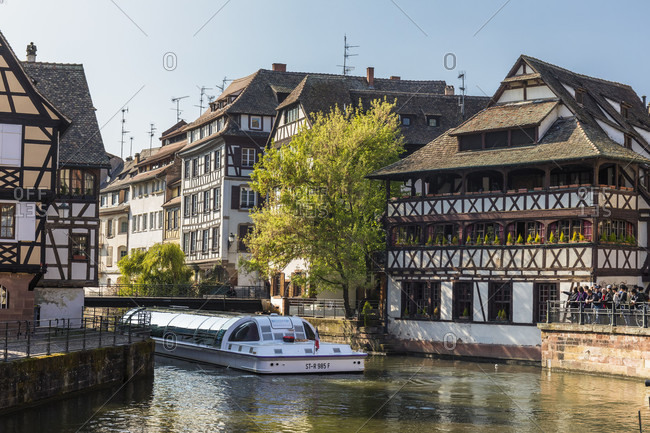 April 7, 2017: Tourist boat on River Ill in front of half-timbered houses at the tanners quarter with Maison de Tanneurs, Petite France, Old City, Strassbourg, Elsass, Grand Est Region, France
