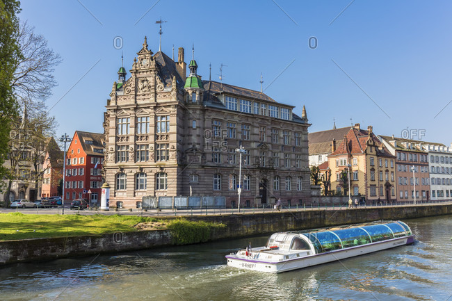 April 8, 2017: Sightseeing boat on River Ille in front of a historic building vom 1898, Old City, Strasbourg, Elsass, Grand Est Region, France