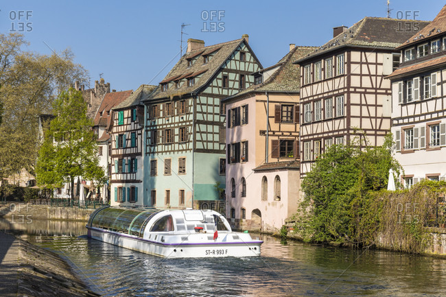 April 8, 2017: Sightseeing boat on River Ille in front of half-timbered houses, Petite France, Old City, Strasbourg, Elsass, Grand Est Region, France