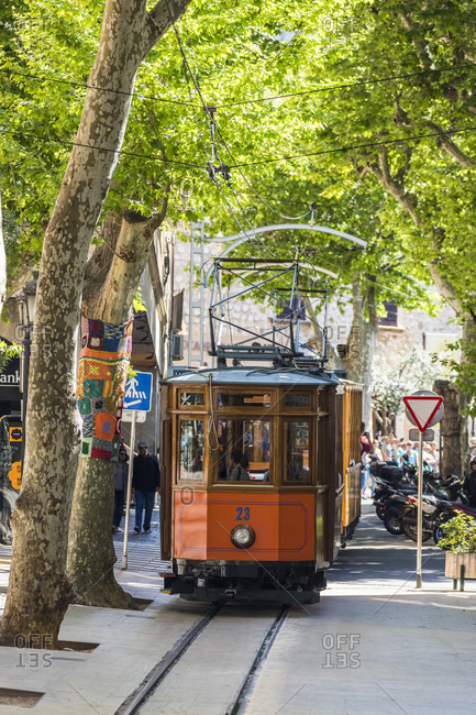 April 22, 2017: Historic tram on a street beneath a light spring foliage roof, Soller, Sierra de Tramuntana, Mallorca, Balearic Islands, Spain