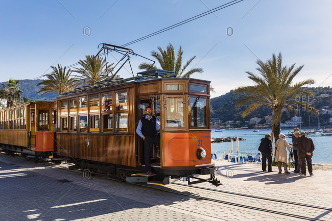 April 22, 2017: Historic tram in front of Palm trees along the promade, Port de Soller, Mallorca, Balearic Islands, Spain