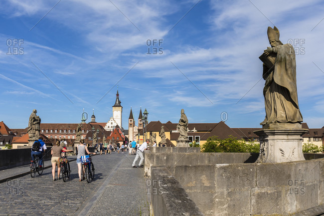June 12, 2017: View of the old Main Bridge (Alte Mainbruecke) with its figures of saints, the tower of Grafeneckart and old Town Hall and St. Kilian Cathedral, Wuerzburg, Lower Franconia, Bavaria, Germany