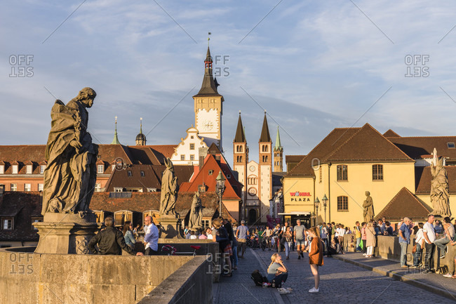 June 12, 2017: People on the old Main Bridge (Alte Mainbruecke) with its figures of saints, the tower of Grafeneckart and old Town Hall and St. Kilian Cathedral, sunset, Wuerzburg, Lower Franconia, Bavaria, Germany