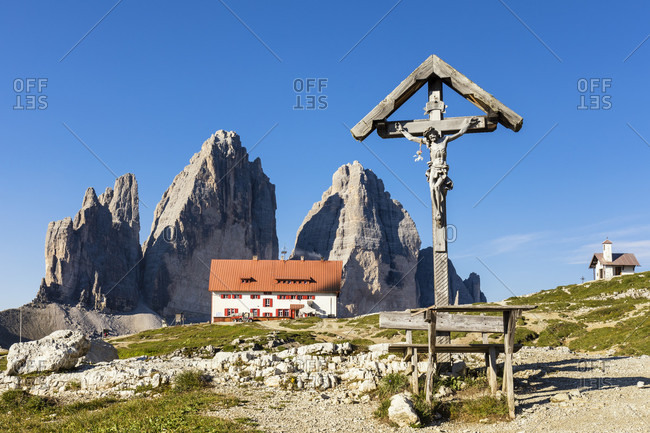 Old wooden cross in front of the Rifugio Tre Cime di Lavaredo-A. Locatelli (Dreizinnenhütte) and the Tre Cime di Lavaredo, Drei Zinnen (2999m), Dolomiti di Sesto Natural Park, Alta Pusteria, Bolzano district, South Tyrol, Alps, Dolomites, Trentino-Alto Adige, Italy