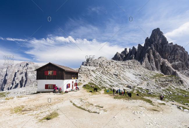 July 19, 2017: Hiker nearby a small hut at the Rifugio Tre Cime di Lavaredo-A. Locatelli in front of the Paternkofel (2744m), Drei Zinnenhütte, Dolomiti di Sesto Natural Park, Alta Pusteria, Bolzano district, South Tyrol, Alps, Dolomites, Trentino-Alto Adige, Italy