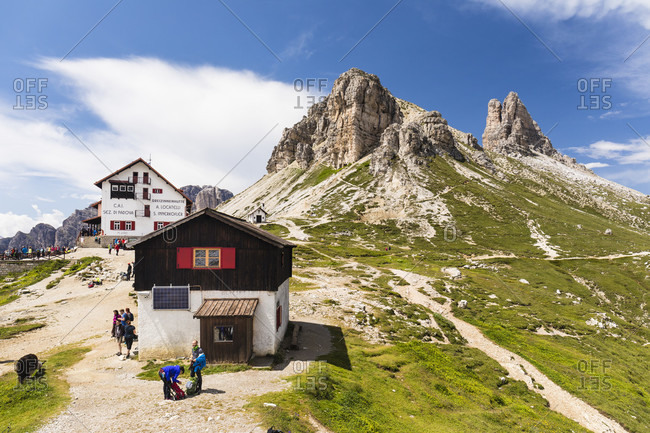 May 15, 2015: Hiker nearby a small hut and the Rifugio Tre Cime di Lavaredo-A. Locatelli, Drei Zinnenhütte, in front of Toblinger Knoten (2617m), Dolomiti di Sesto Natural Park, Alta Pusteria, Bolzano district, South Tyrol, Alps, Dolomites, Trentino-Alto Adige, Italy