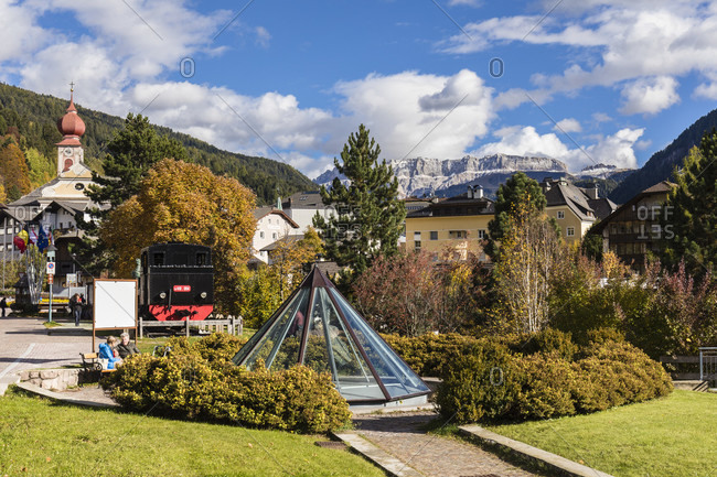 October 8, 2017: People relaxing in a little park by a historic steam train at the former railway station, St. Ulrich in Groden, Groeden Valley, Dolomites, TrentinoAlto Adige, South Tyrol, Italy