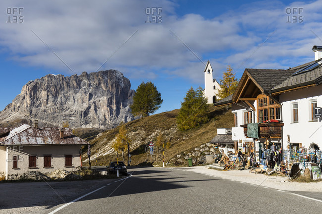 October 9, 2017: Capella di San Maurizio and buildings on Gardena Pass (Groedner Joch) in front of Langkofel (3181m), autumn, Dolomites, TrentinoAlto Adige, South Tyrol, Italy