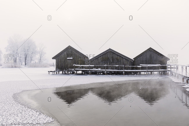 Three boat houses during fog on the partly frozen Lake Kochelsee, winter, Schlehendorf, Kochel am See, Oberbayern, Bavaria, Germany