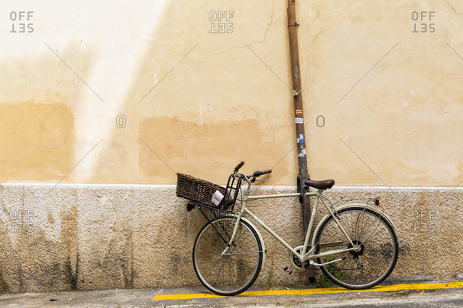 Bicycle with a front basket by a wall and yellow line on the ground, Old City, Palma de Mallorca, Mallorca, Balearic Islands, Spain