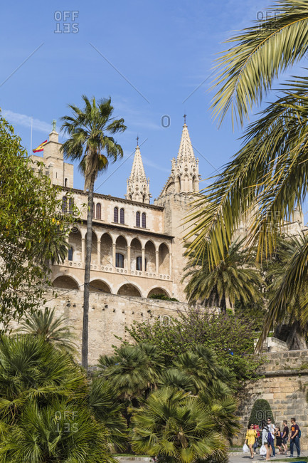April 26, 2017: Palm trees and L'Almudaina an the towers of La Seu Cathedral, Old City, Palma de Mallorca, Mallorca, Balearic Islands, Spain