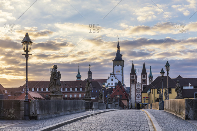 June 13, 2017: View of the old Main Bridge (Alte Mainbruecke) with its figures of saints, the tower of Grafeneckart and old Town Hall and St. Kilian Cathedral at sunrise, Wuerzburg, Lower Franconia, Bavaria, Germany