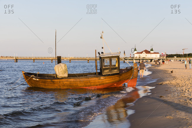 June 19, 2017: Fishing boat on the beach in front of the pier of the Seaside Resort Ahlbeck, Usedom Island, Mecklenburg-Vorpommern, Mecklenburg-Western Pomerania, Germany