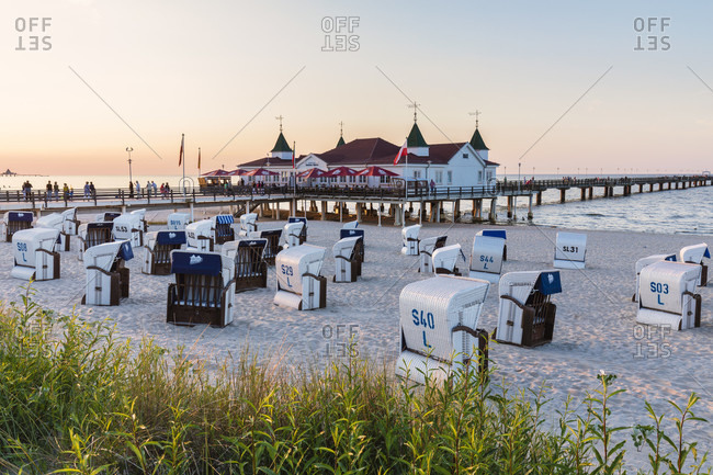 June 19, 2017: Roofed beach wicker chairs on the beach in front of the pier of the Seaside Resort Ahlbeck, Usedom Island, Baltic Sea, Mecklenburg-Vorpommern, Mecklenburg-Western Pomerania, Germany