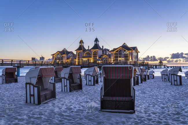 May 15, 2015: Roofed wicker charis in front of the illuminated pier of the Baltic Seaside Resort of Sellin, dawn, Ruegen Island, Insel Rügen, Baltic Sea, Mecklenburg-Vorpommern, Mecklenburg-Western Pomerania, Germany