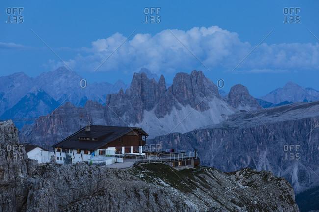 July 15, 2017: Lagazuoi Refuge in front of Croda da Lago (2700m), Monte Pelmo (3168m), Averau (2649m) and Antelao (3264m), dusk, blue hour, Cortina d'Ampezzo, Cadore, Belluno district, Dolomites, Veneto, Italy