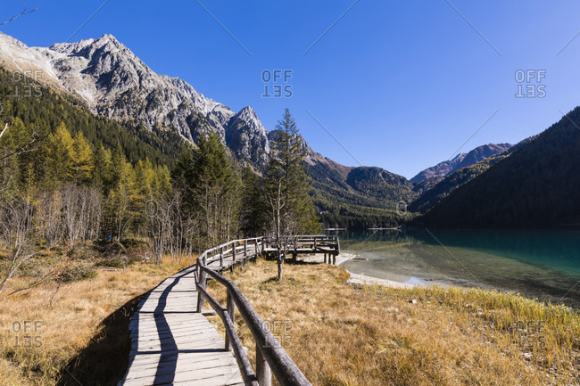 The new experience of nature path at Anterselva lake in autumn in front of the Mountains of the Nature Park Rieserferner-Ahrn, Valle di Anterselva, Pusteria Valley, Dolomites, Bolzano district, South Tyrol, TrentinoAlto Adige, Italy