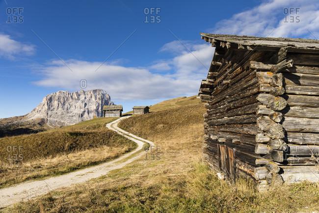 Langkofel Mountain and hay barns in autumn on Gardena Pass, Groedner Joch, Dolomites, TrentinoAlto Adige, South Tyrol, Italy