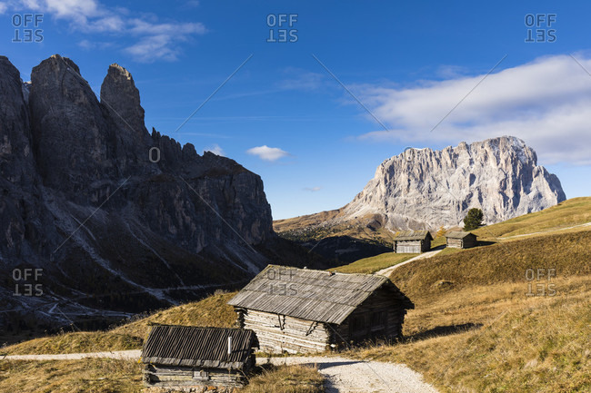 Huts in front of a silhouette of the Sella Towers (2696m) in the Sella Group and Langkofel (3181m) in an autumnal landscape, Gardena Pass, Groedner Joch, Dolomites, TrentinoAlto Adige, South Tyrol, Italy