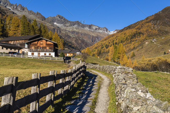 Stonewall framed path leading to St. Spiritu Chapel, Church of the Holy Spirit from 15th Century, autumn, Kasern, Ahrntal Valley, Pusteria Valley, Dolomites, Bolzano district, TrentinoAlto Adige, South Tyrol, Italy