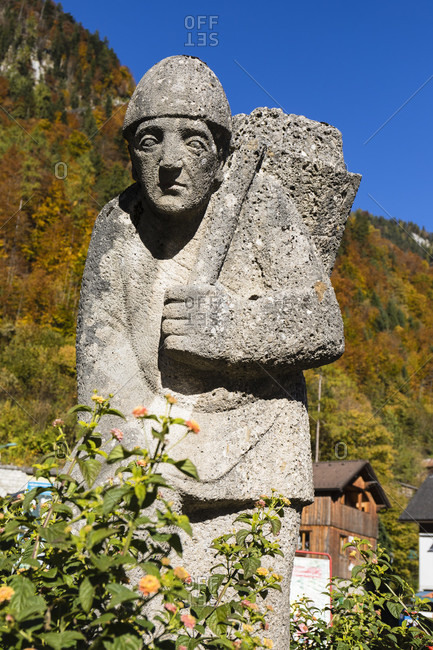 October 16, 2017: Sculpture of a man carrying salt on his shoulder at the town of Hallstatt on Lake Hallstatt in autumn, UNESCO World Heritage Site, Salzkammergut, Upper Austria, Austria