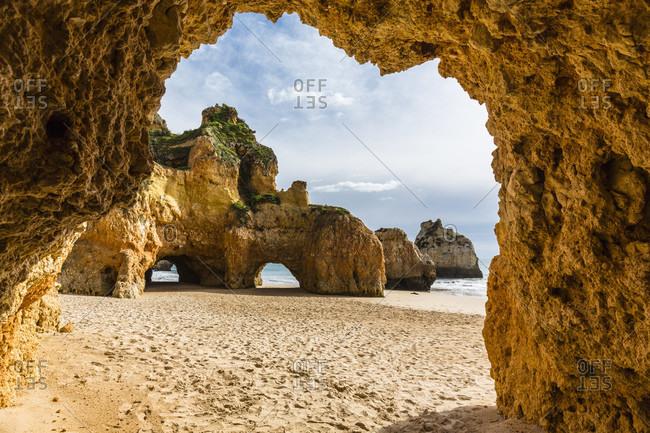 Praia de Tres Irmaos, view through natural stone arch, Alvor, Portimao, Algarve, Portugal