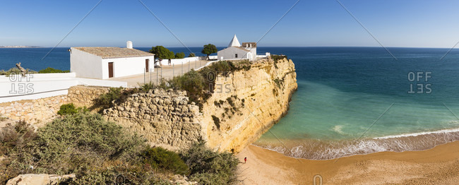 White chapel Nossa Senhora da Rocha on a rocky cliff above the beach
