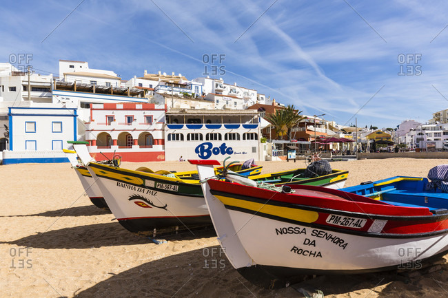 May 9, 2015: Fishing boats on the Praia de Carvoeiro in front of colorful buildings