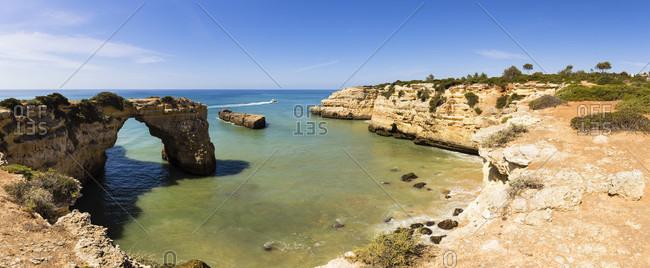 Sea Arch by a small sand beach beneath steep cliffs