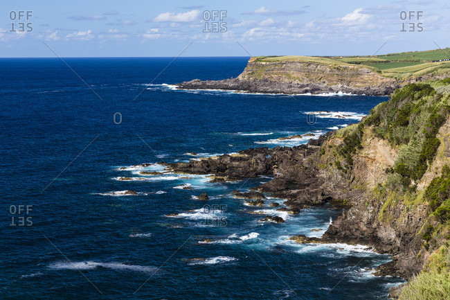 Steep rocky lava coast and the surf in the Atlantic Ocean