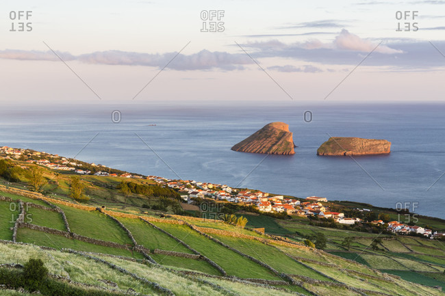 Agricultural land with lava stone walls in front of the view to the Ilheus das Cabras, sunset, Serra da Ribeirinha