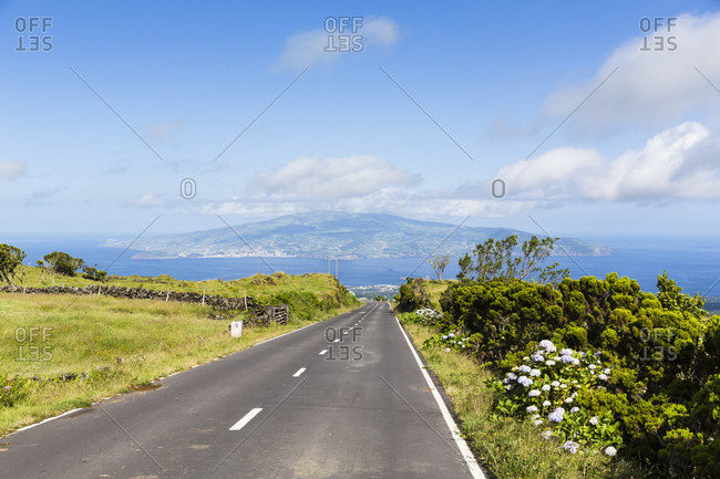 Road going through pastureland in front of a view to Faial in the distance
