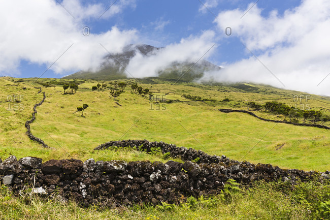 Lava stone wall in front of pastureland and the cloud covered Mount Pico