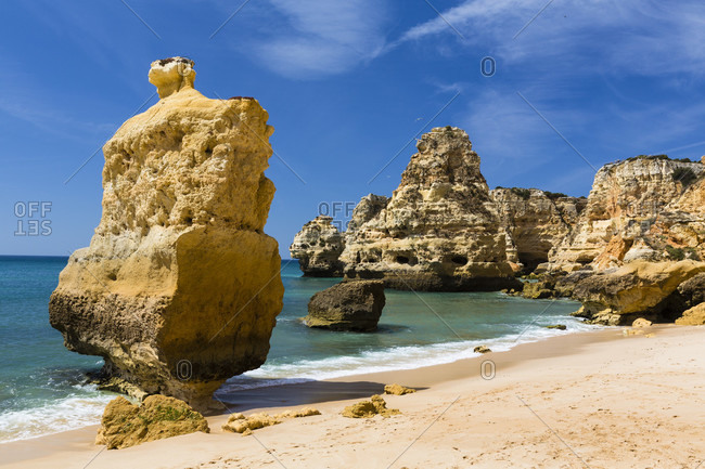 People sunbathing among rock formations on Praia da Marinha