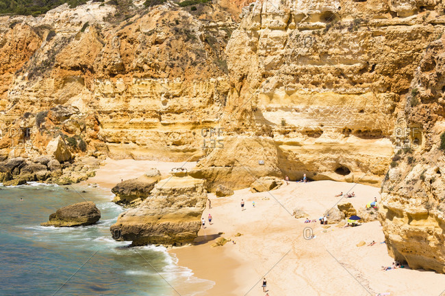 May 15, 2015: People sunbathing among rock formations on Praia da Marinha, elevated view