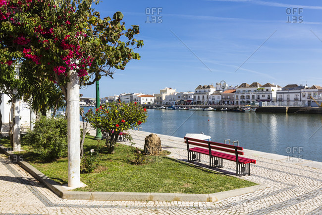 May 10, 2015: Red benches, palm trees and blooming Bouganvillea at a riverside park, Gilao River and Old town in the background