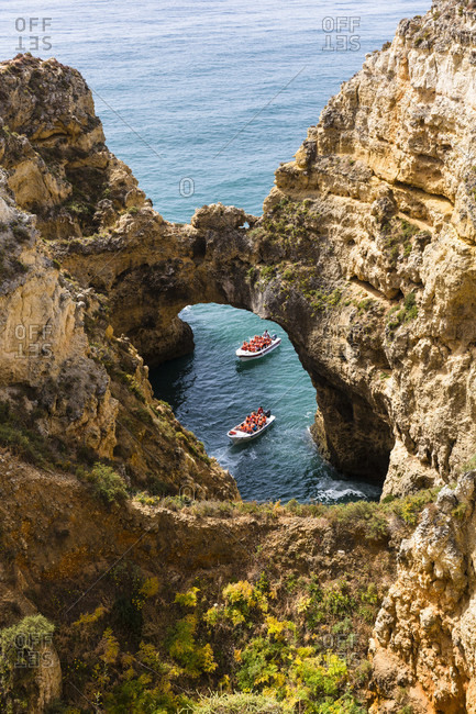 High angele view on boats in a hole of the rock fromations at Ponta da Piedade