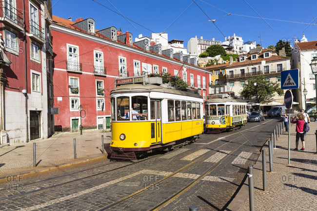 May 16, 2015: Historic old yellow tram at Largo das Portas do Sol in front of colorful city buildings, Alfama district, Alfama district, Lisbon, Portugal
