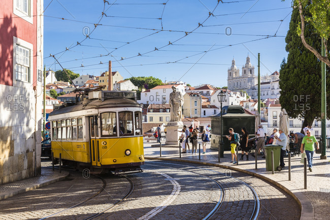 May 16, 2015: Old tram on a narrow street in front of the Statue of Sao Vicente and the Grace Convent, Largo das Portas do Sol, Alfama district