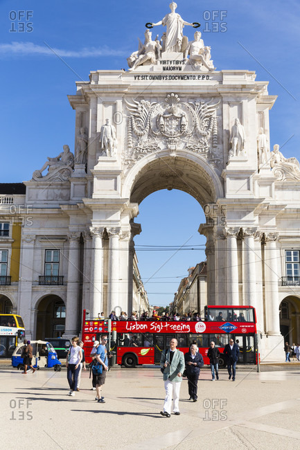 May 15, 2015: Red open roof sightseeing bus in Praca do Comercio at the Rua Augusta Arch (Arco Triunfal), Baixa district, Lisbon, Portugal