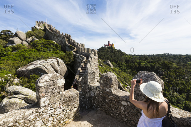 Young woman with white hat enjoying the view from Castelo dos Mouros to the Pena National Palace, UNESCO World Heritage Site, Sintra, Portugal