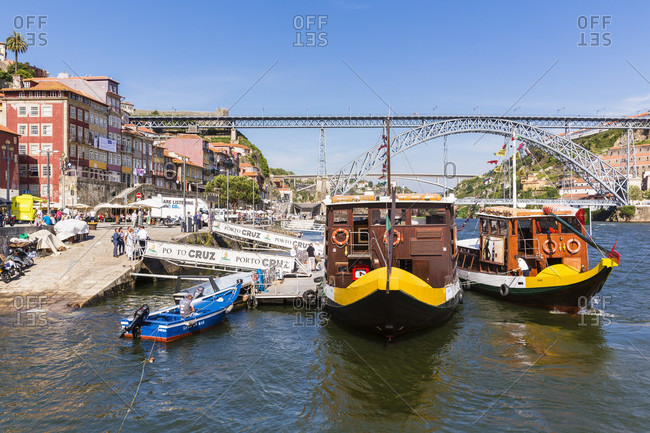 May 18, 2015: Traditional port wine boats on the Douro River in front of the Ponte de Dom Luis I Bridge, historic district, UNESCO World Heritage Site
