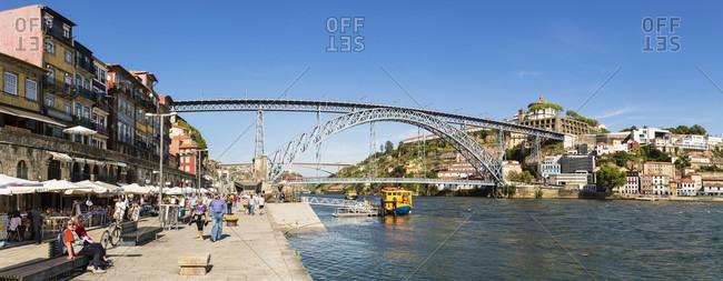May 18, 2015: Promenade at the Douro River in front of the Ponte de Dom Luis I Bridge, historic district, UNESCO World Heritage Site