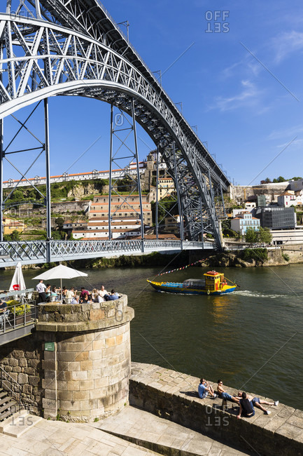 May 18, 2015: Sightseeing boat on the Douro River in front of the Ponte de Dom Luis I Bridge, historic district, UNESCO World Heritage Site