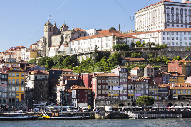 May 18, 2015: Cathedral (Terreiro da Se) above the old town Cais da Ribeira, historic district and traditional port wine boats on the Douro River, Cais de Gaia, UNESCO World Heritage Site