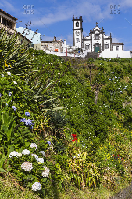 Parish church above a steep Hortensia and flower covered slope