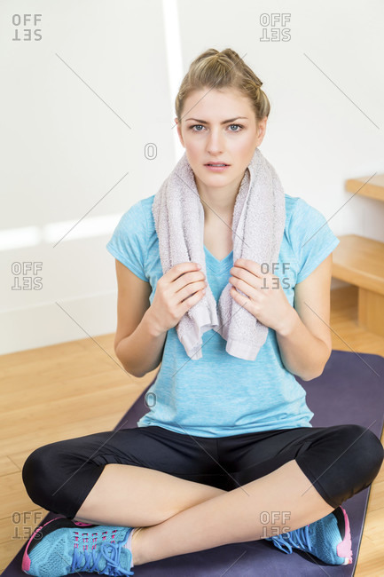 Cute young blond woman in sportswear sitting on a yoga mat portrait